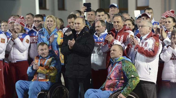 Russia's President Vladimir Putin stands near members of the Russian Paralympic team as he visits the mountain village on the eve of the opening of the 2014 Sochi Paralympic Winter Games in Krasnaya Polyana