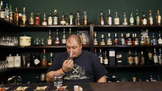 """In this Thursday, April 25, 2013 photo Petr Nemy, an whisky expert, tastes the single malt """"Hammer Head"""" whisky in a bar in Prague, Czech Republic. The """"Hammer Head"""" whisky made in communist Czechoslovakia matured in oak barrels for more than twenty years to reach surprisingly good quality before hitting the market. (AP Photo/Petr David Josek)"""