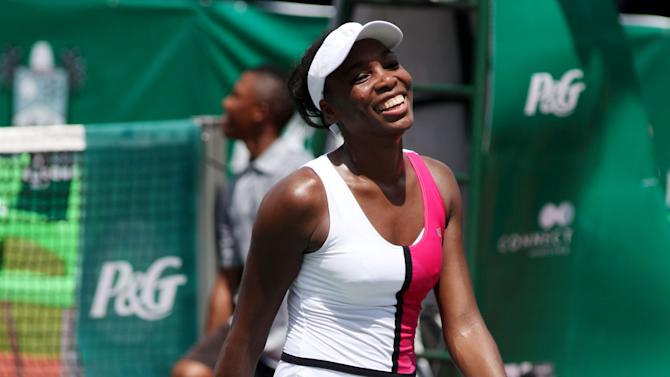 """Venus Williams of the U.S. smiles after defeating her sister Serena during an exhibition tennis match against in Lagos, Nigeria, Friday, Nov. 2, 2012. A dancing, smiling Venus Williams topped her sister Serena in an exhibition match in Nigeria's largest city, saying her win showed 2013 """"is going to be a great year."""" (AP Photo/Sunday Alamba)"""
