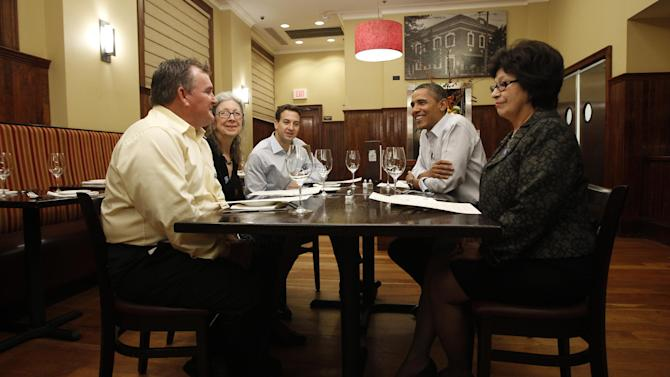 """President Barack Obama has dinner with campaign donors and winners of the  """"Dinner with Barack"""" contest at The Liberty Tavern in the Clarendon neighborhood of Arlington, Va., Thursday, Oct. 27, 2011. From left to right: Ken Knight, U.S. postal worker from Chandler, Ariz.; Wendi Smith, artist and retired professor from Corydon, Ind.; Casey Helbling, enterpreneur from Minneapolis, Minn.; President Obama; Juanita Martinez, retired teacher from Brighton, Colo. (AP Photo/Charles Dharapak)"""