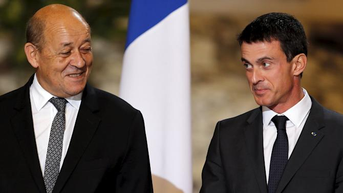 French Prime Minister Manuel Valls stands with French Defence minister Jean-Yves Le Drian  during a ceremony to sign military contracts with Egypt's President Abdel Fattah al-Sisi at the Ittihadiya presidential palace in Cairo
