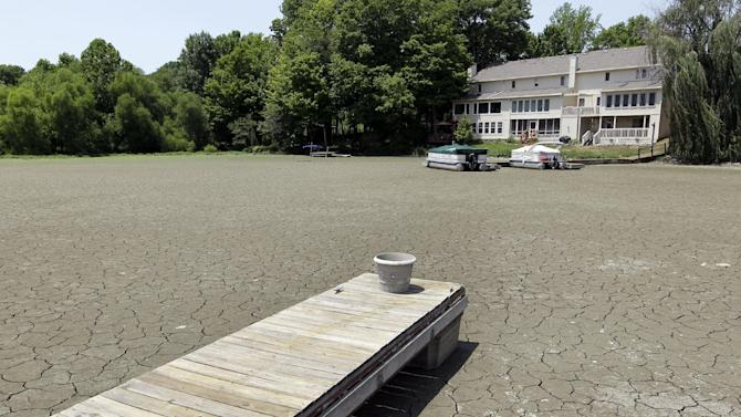 FILE - In this July 5, 2012 file photo, a dock extends into a dry cove at Morse Reservoir in Noblesville, Ind., as oppressive heat and drought conditions stifle the middle of the United States. In 2012 many of the warnings scientists have made about global warming went from dry studies in scientific journals to real-life experience. One example: July was the hottest month in record-keeping U.S. history. (AP Photo/Michael Conroy, File)