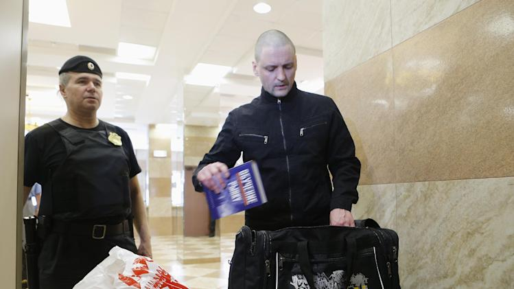 Opposition leader Sergei Udaltsov has his belongings checked as he arrives at a court building in Moscow