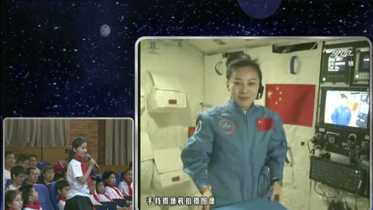 In this image taken June 20, 2013 and made from CCTV, Chinese astronaut Wang Yaping, seen on screen, listens to a question from a school girl in Beijing, China, during a live broadcast from onboard the Tiangong 1 prototype space station. Astronauts struck floating martial arts poses, twirled gyroscopes and manipulated wobbling globes of water during a lecture Thursday from China's orbiting space station that's part of efforts to popularize the space program among young people. (AP Photo/CCTV via AP Video) CHINA OUT, TV OUT