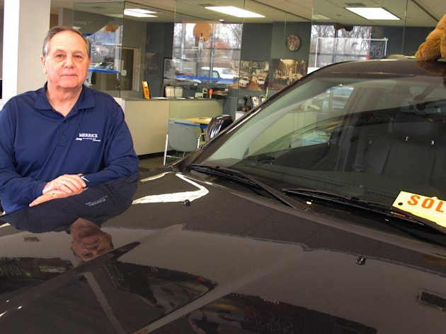 Joe Settineri , owner of Merrick Dodge Chrysler Jeep of Wantagh, N.Y., stands beside a recently sold Jeep. The car dealer says sales have been extraordinary in the weeks since Superstorm Sandy, as tho