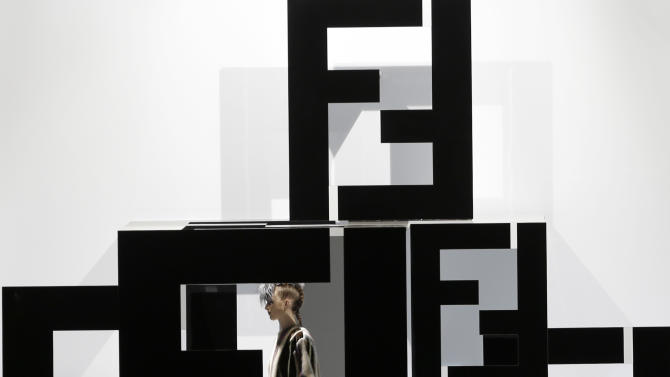 A model is seen through a giant Fendi logo on the catwalk during Fendi women's Fall-Winter 2013-14 collection, part of the Milan Fashion Week, unveiled in Milan, Italy, Thursday, Feb. 21, 2013. (AP Photo/Luca Bruno)