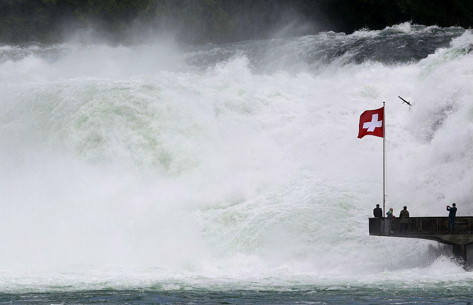 Visitors stand on a platform beside the Rhine Falls in the town of Neuhausen south of Schaffhausen June 13, 2012. The Rhine Falls are the largest falls in Europe, with an average flow of 700 m3 per se