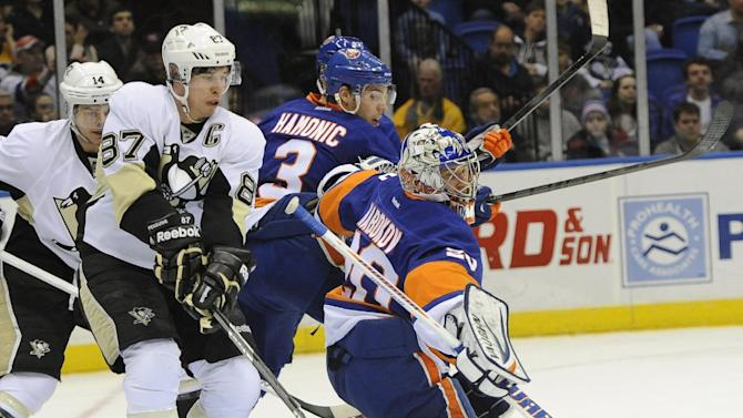 New York Islanders goalie Evgeni Nabokov (20) drives the puck away from Pittsburgh Penguins' Sidney Crosby (87) during the first period of an NHL hockey game on Friday, March 22, 2013 at Nassau Coliseum in Uniondale, N.Y. (AP Photo/Kathy Kmonicek)