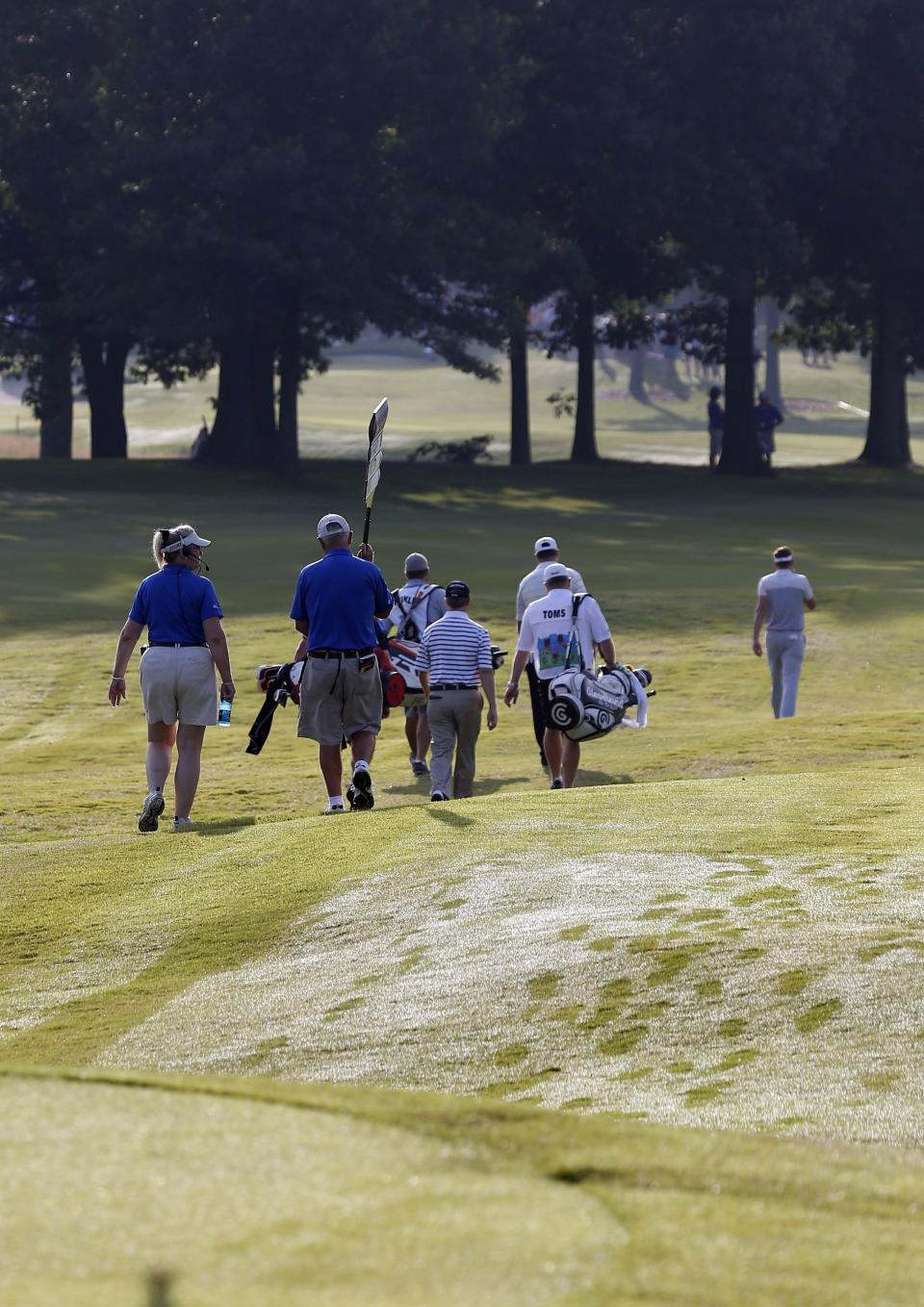 Boo Weekley, Ian Poulter and David Toms leave their footprints in the dew covered greens on 10th hole during the opening round of the St. Jude Classic golf tournament Thursday, June 6, 2013, in Memphis, Tenn. (AP Photo/Rogelio V. Solis)