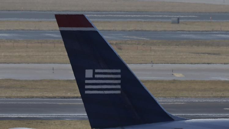 An American Airlines jet taxis past a US Airways jet at the Philadelphia International Airport, Thursday, Feb. 14, 2013, in Philadelphia. The merger of US Airways and American Airlines has given birth to a mega airline with more passengers than any other in the world. (AP Photo/Matt Rourke)