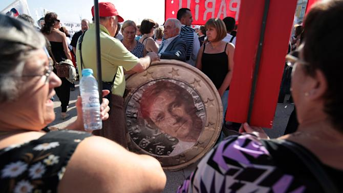 Protestors stand by a mock Euro coin with a photo of Portuguese Prime Minister Pedro Passos Coelho during a workers unions' demonstration in Lisbon, Saturday, Sept. 29 2012. Thousands of Portuguese enduring deep economic pain from austerity cuts took to the streets Saturday in protest. (AP Photo/Armando Franca)