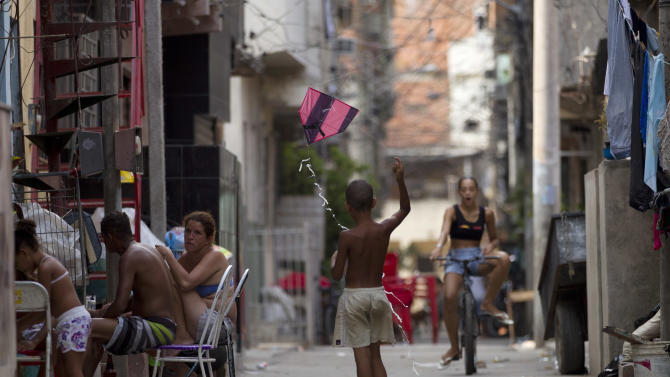 In this Dec. 28, 2012 photo, a child flies a kite in the Mare shantytown in Rio de Janeiro, Brazil. The city's densest neighborhoods, its favelas, or shantytowns blanket entire hillsides, providing most of the city's affordable housing. Now, those communities are being charted after decades of informality, each route and alley outlined and their names researched. A nonprofit organization run by current and former favela residents called Redes da Mare kick-started the first mapping program in the grouping of favelas known as Mare with a simple but powerful goal: putting their homes on the map, with named streets, zip codes and official addresses. (AP Photo/Silvia Izquierdo)