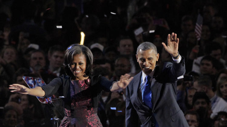 FILE - This file photo taken Nov. 6, 2012 in Chicago shows President Barack Obama along with first lady Michelle Obama acknowledging the crowd at his election night party. As Michelle Obama stepped on stage , she accepted her role not only as first lady but fashion tastemaker for four more years.(AP Photo/Nam Y. Huh, file)