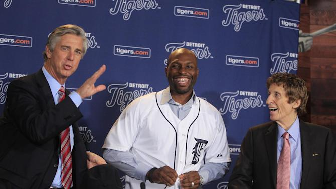 New Detroit Tigers outfielder Torii Hunter, smiles after putting on his jersey as team general manager David Dombrowski, left, and owner Mike Ilitch look on before a news conference in Detroit, Friday, Nov. 16, 2012. Hunter, who last played for the Los Angeles Angels, signed a two-year, $26 million deal. (AP Photo/Carlos Osorio)