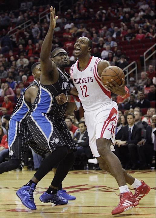 Houston Rockets power forward Dwight Howard (12) is fouled by Orlando Magic's Jason Maxiell (54) as he attempts to drive during the second half of an NBA basketball game on Sunday, Dec. 8, 2013, i