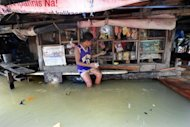 A boy makes a purchase in a flooded convinient store in Manila. Four people were killed as another tropical storm swept across the Philippines on Wednesday, triggering landslides in the mountainous north and dumping more heavy rain on the flood-battered capital