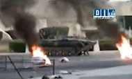 An image grab from a video uploaded on YouTube shows a Syrian army tank driving past burning tires in the city of Hama, where human rights activists said more than 90 people were killed as the Syrian military launched an attack on the flashpoint city. Note: AFP is not authorized to cover this event and is therefore using pictures from alternative sources, which cannot be independently verified
