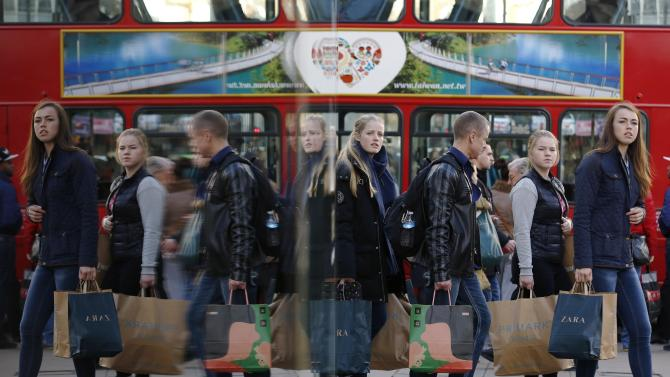 Shoppers are reflected in a window as they carry bags along Oxford street during the final weekend of shopping before Christmas in London