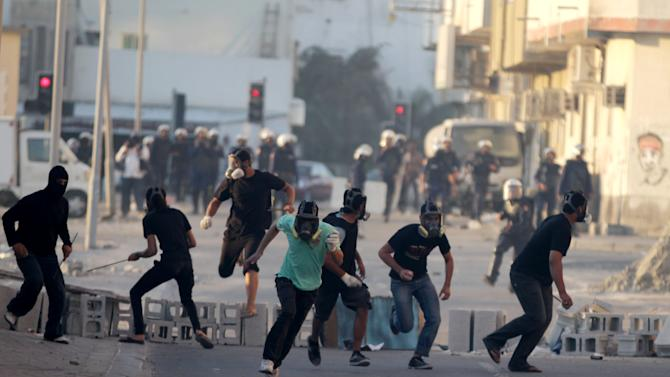 Bahraini anti-government protesters, masked against tear gas and some carrying steel rods, run from riot police in Sitra, Bahrain, on Wednesday, March 27, 2013. Clashes erupted after the politically charged funeral of Jaffar al-Taweel, 35, who relatives and rights activists say died from excessive tear gas inhalation. (AP Photo/Hasan Jamali)