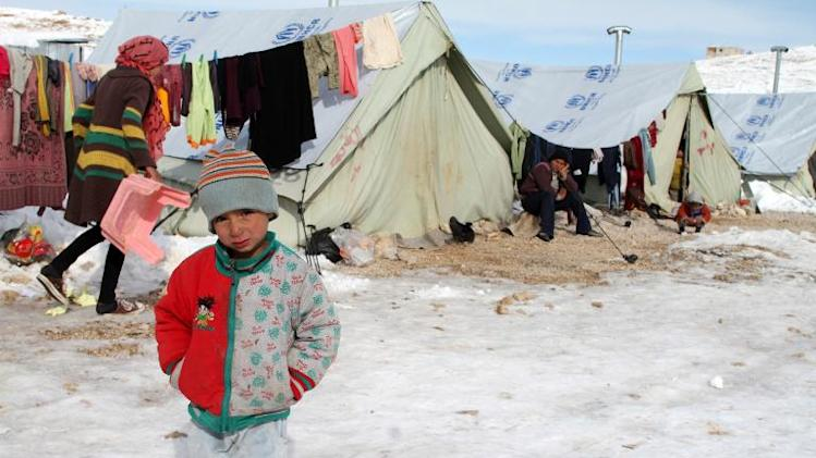 A Syrian child stands in the snow in a refugee camp in the town of Arsal in the Lebanese Bekaa valley on December 13, 2013