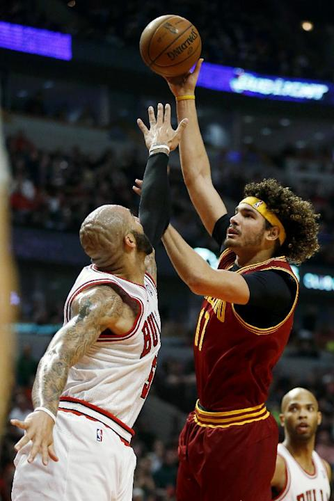 Cleveland Cavaliers center Anderson Varejao (17) shoots over Chicago Bulls forward Carlos Boozer (5) during the first half of an NBA basketball game on Saturday, Dec. 21, 2013, in Chicago