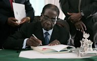 Zimbabwe President Robert Mugabe signs into law Zimbabwe's new constitution at the State House in Harare on May 22 2013, clearing the path to crucial elections later this year