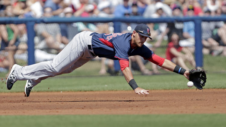 Boston Red Sox third baseman Will Middlebrooks (16) dives for a line drive single by Tampa Bay Rays Yunel Escobar in the first inning of an exhibition baseball game in Port Charlotte, Fla., Sunday, March 16, 2014