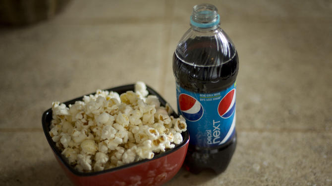 In this Monday, Oct. 15, 2012, photo,  a bottle of  Pepsi is displayed next to popcorn in Pembroke Pines, Fla.  PepsiCo Inc.'s net income dipped 5 percent in the third quarter, as the food and beverage maker poured more money into bolstering its flagship brands and developing new products that cater to shifting consumer tastes. (AP Photo/J Pat Carter)