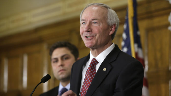 Arkansas Gov. Asa Hutchinson answers reporters' questions as Sen. Jonathan Dismang, R-Beebe, background, listens at the state Capitol in Little Rock, Ark., Wednesday, April 1, 2015. Hutchinson called for changes to the state's religious objection measure facing a backlash from businesses and gay rights groups, saying it wasn't intended to sanction discrimination based on sexual orientation. (AP Photo/Danny Johnston)