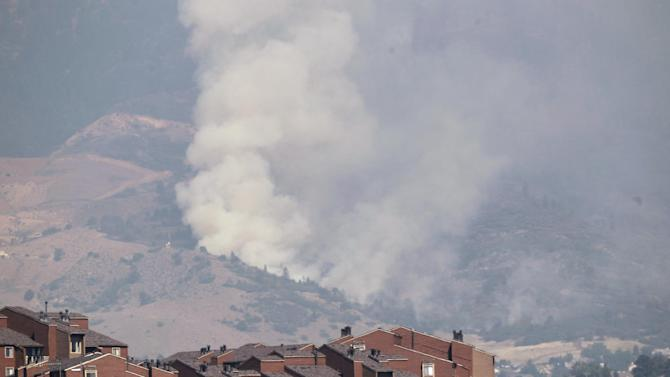 A plume of smoke rises behind homes on the Waldo Canyon wildfire west of Colorado Springs, Colo., on Wednesday, June 27, 2012. A large number of homes were destroyed by the fire Tuesday night in subdivisions west of Colorado Springs.  Authorities say it remains too dangerous for them to fully assess the damage from a destructive wildfire threatening Colorado's second-largest city.  (AP Photo/Ed Andrieski)