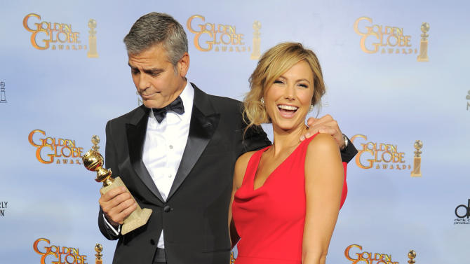 """Actor George Clooney, left, poses backstage with the award for Best Actor in a Motion Picture Drama for the film """"The Descendants"""" with Stacy Keibler during the 69th Annual Golden Globe Awards Sunday, Jan. 15, 2012, in Los Angeles. (AP Photo/Mark J. Terrill)"""
