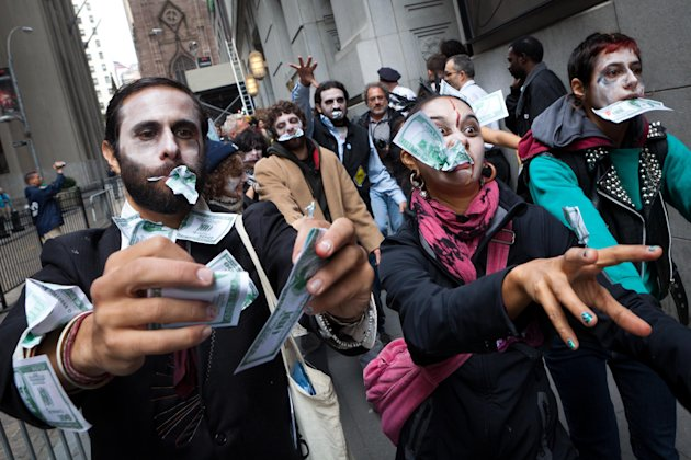 "Protesters from Occupy Wall Street march through New York's financial district dressed as ""corporate zombies"" Monday, Oct. 3, 2011. The protests have gathered momentum and gained participants in recen"