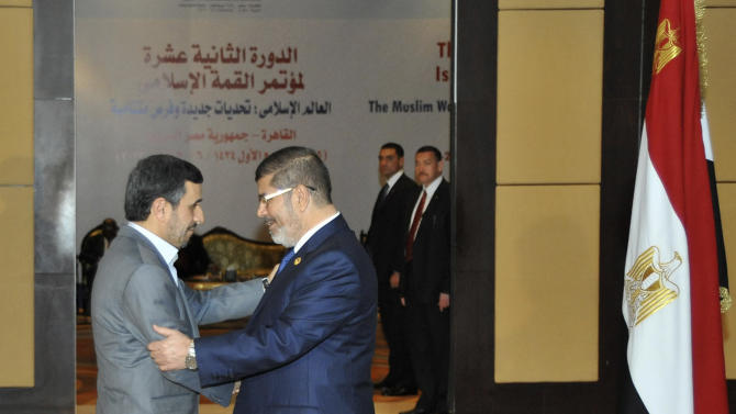 "In this picture released by the Egyptian Presidency, Mohammed Morsi, right, embraces Iranian President Mahmoud Ahmadinejad, left, at the 12th summit of the Organization of Islamic Cooperation in Cairo, Egypt, Wednesday, Feb. 6, 2013. Iran's president on Wednesday offered to help rescue Egypt's failing economy with a ""big credit line,"" another sign of improving relations between two regional powers after a freeze of more than three decades. Ahmadinejad made the proposal during the first trip to Egypt by an Iranian leader since 1979. It came at a time when his own economy is staggering from the effects of Western sanctions over Iran's suspect nuclear development program, and it was unclear how he could spare funds or credit for his new ally. (AP Photo/ Egyptian Presidency)"