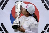 South Korean professional golfer Park Inbee kisses the trophy in front of the south korean flag after winning the Evian Masters Golf Tournament in Evian-les-Bains, French Alps. Park had a magical day with the putter to hold off a bunch of players and win the Evian Masters with a fantastic closing 66 here on Sunday