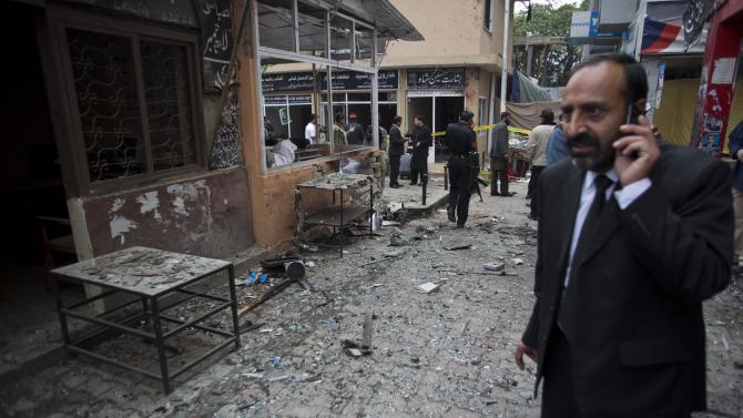 A Pakistani lawyer talks on his mobile phone at the site of a suicide attack in a court complex, Monday, March 3, 2014 in Islamabad, Pakistan. Two suicide bombers blew themselves up at the complex on Monday, killing 11 people and wounding dozens in a rare terror attack in the heart of Islamabad, officials said. (AP Photo/B.K. Bangash)