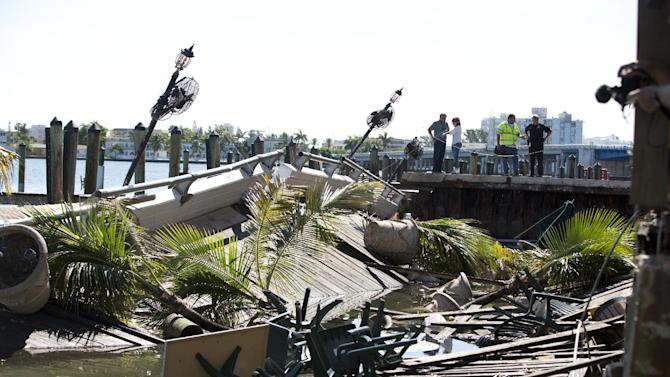Officials begin their inspection of the outdoor deck that collapsed at Shuckers Bar and Restaurant, Friday, June 14, 2013 . The packed outdoor deck behind the popular Miami-area sports bar partially collapsed during the NBA Finals on Thursday night, sending dozens of patrons into the shallow waters of Biscayne Bay. (AP Photo/J Pat Carter)