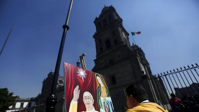 A man paints a picture of Pope Francis outside Metropolitan Cathedral in Mexico City