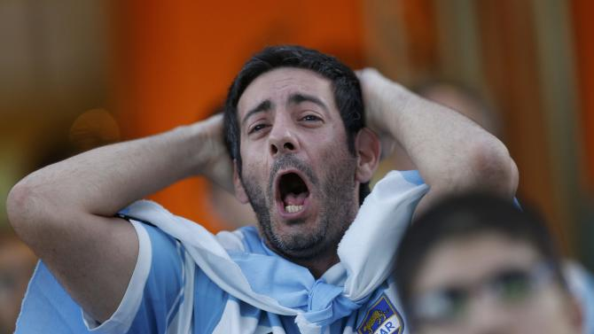 A fan of Argentina reacts while watching a broadcast of the 2014 World Cup final against Germany at the Argentine Embassy in Brasilia