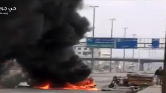 This image taken from video obtained from Ugarit News on Friday, Feb. 8, 2013, which has been authenticated based on its contents and other AP reporting, show smoke and fire rising on a main highway in Damascus, Syria. Rebels pushed forward in their battle with the Syrian army in northeastern Damascus on Friday, shutting down a main highway with a row of burning tires, activists said. A number of rebel brigades launched a campaign Wednesday to attack regime checkpoints along the highway and have been clashing in the area since. The government has responded by shelling number of rebel areas nearby. (AP Photo/Ugarit News via AP video)