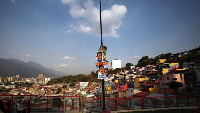 """Posters of late Venezuela's President Hugo Chavez and acting President Nicolas Maduro hang at a lamp post outside a people's shrine in honor of Chavez at the """"23 de Enero"""" or """"23rd of January"""" slum in Caracas, Venezuela, Wednesday, April 3, 2013. The shrine, named  """"Saint Hugo Chavez del 23"""", has been visited by tens of thousands of Venezuelans to pay homage to a president for some, a saint for others. (AP Photo/Fernando Llano)"""