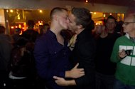 """Two men kiss shortly after midnight during a celebration for the end of the policy commonly known as """"don't ask, don't tell"""" in the military Tuesday, Sept. 20, 2011, in San Diego. After years of debate and months of final preparations, the military can no longer prevent gays from serving openly in its ranks. (AP Photo/Gregory Bull)"""
