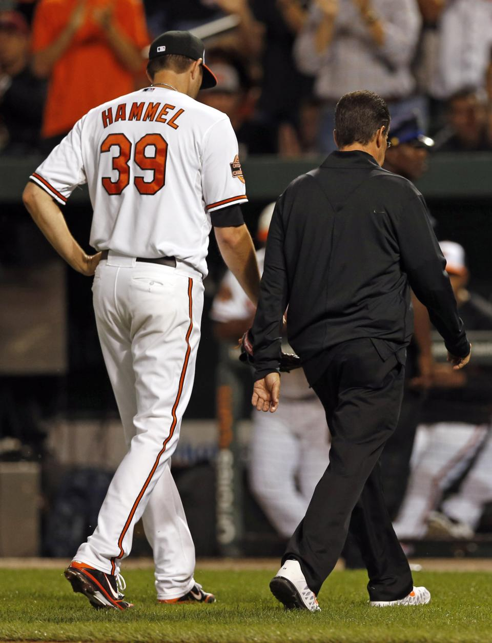 Baltimore Orioles starting pitcher Jason Hammel, left,  walks off the field with trainer Richie Bancells after he injured his right knee in the fourth inning of a baseball game against the Tampa Bay Rays in Baltimore, Tuesday, Sept. 11, 2012. (AP Photo/Patrick Semansky)