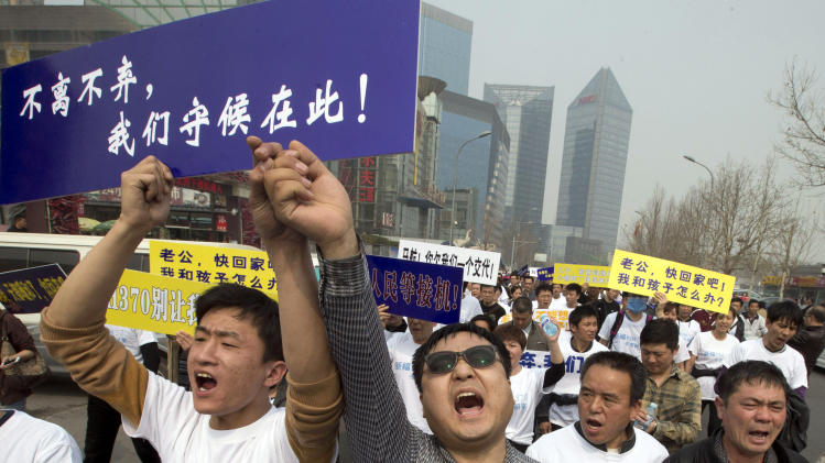 """FILE - In this Tuesday, March 25, 2014 file photo, Chinese relatives of passengers onboard the missing Malaysia Airlines plane, flight MH370, shout in protest as they march towards the Malaysia embassy in Beijing, China. Authorities have been forced on the defensive by the criticism, the most forceful of which has come from a group of Chinese relatives who accuse them of lying about - or even involvement in - the disappearance of Flight 370. The blue placard reads: """"We won't leave or ditch you, we will wait right here."""" (AP Photo/Ng Han Guan, File)"""