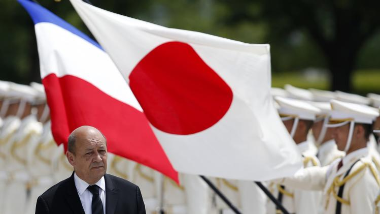 Le Drian reviews honor guards at the Defense Ministry in Tokyo