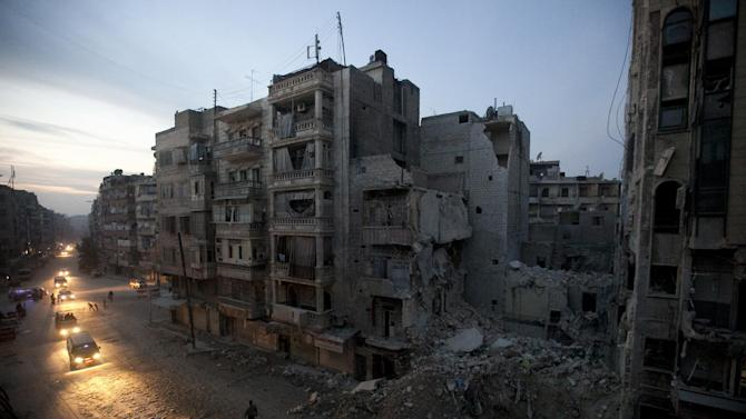 FILE - In this Nov. 29, 2012 file photo, Night falls on a Syrian rebel-controlled area of Aleppo, as destroyed buildings, including Dar Al-Shifa hospital, are seen on Sa'ar street after airstrikes targeted the area a week before. More than 100,000 people have been killed since the start of Syria's conflict over two years ago, an activist group said Wednesday. (AP Photo/Narciso Contreras, File)