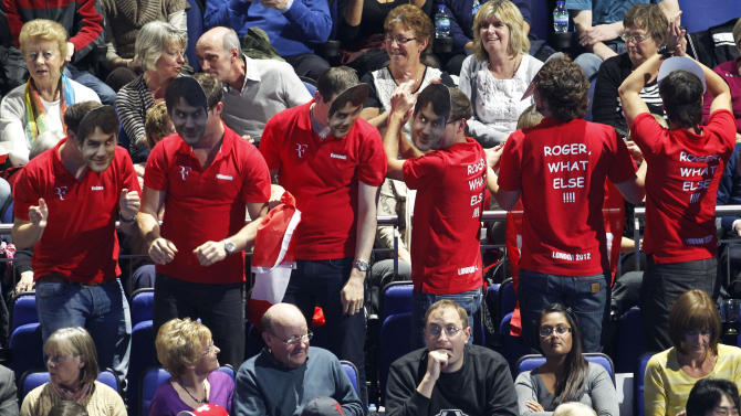 Supporters wearing face masks of Roger Federer cheer on during an ATP World Tour Finals singles tennis match between Roger Federer of Switzerland and Janko Tipsarevic of Serbia at the O2 Arena in London, Tuesday, Nov. 6, 2012. (AP Photo/Sang Tan)