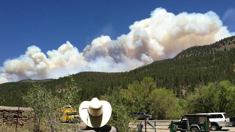 Tracy Bennett, ranch manager of Hidden Valley Ranch, a corporate retreat and guest ranch near Pecos, N.M., watches a large plume of smoke rise from a wildfire Friday, May 31, 2013. Bennett had to evacuate four guests the day before when the fast-moving fire in New Mexico's Santa Fe National Forest threatened the ranch and nearby cabins and vacation homes. (AP Photo/Barry Massey)