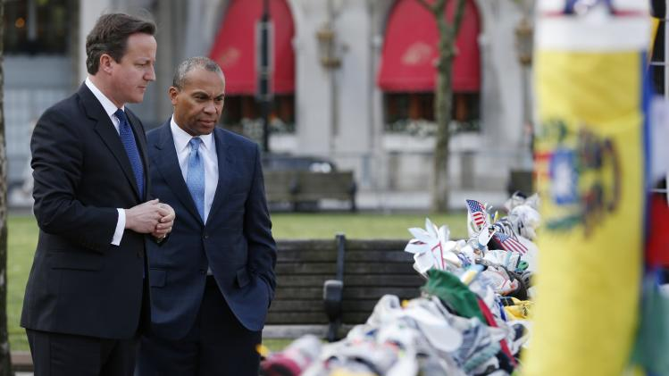 British Prime Minister David Cameron, left, and Massachusetts Gov. Deval Patrick visit the makeshift memorial to the Boston Marathon bombing victims in Copley Square in Boston, Tuesday, May 14, 2013. (AP Photo/Michael Dwyer)