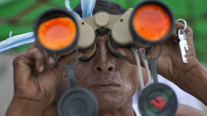 In this Tuesday, Aug. 19, 2014 photo, a man uses a pair of binoculars to get a glimpse of recovery efforts of an ancient bell in the Yangon River in Yangon, Myanmar. Unsubstantiated rumors that the 270-ton mysterious bell has been spotted have sent thousands of curious spectators flocking to the banks of the river. The world's largest copper bell, believed to have been lying deep beneath the riverbed for more than four centuries. (AP Photo/Gemunu Amarasinghe)