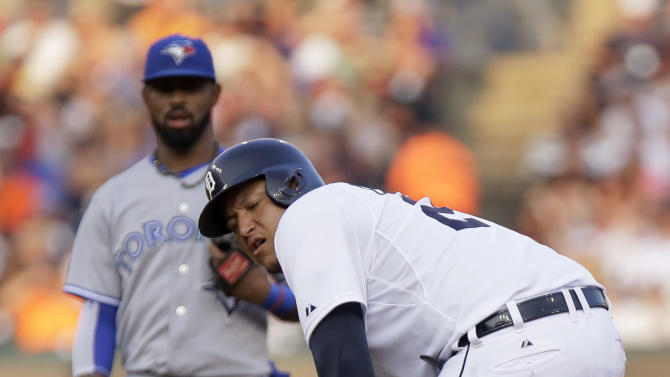 Detroit Tigers' Miguel Cabrera grabs his left leg after a steal attempt during the fourth inning as Toronto Blue Jays' Jose Reyes looks on during a baseball game Friday, July 3, 2015, in Detroit. Cabrera left the game with a strained left calf. (AP Photo/Duane Burleson)